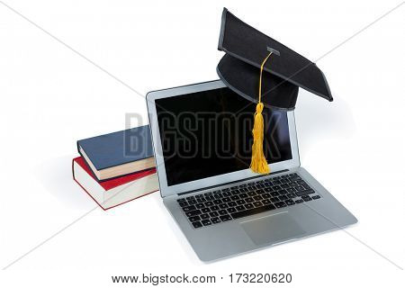 Laptop with mortarboard and books on white background