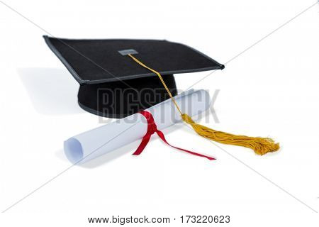 Black graduation cap with degree on white background