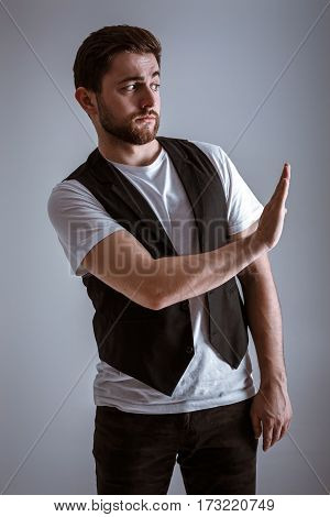 young handsome man with a beard in a white shirt and a black waistcoat shows the gesture stop