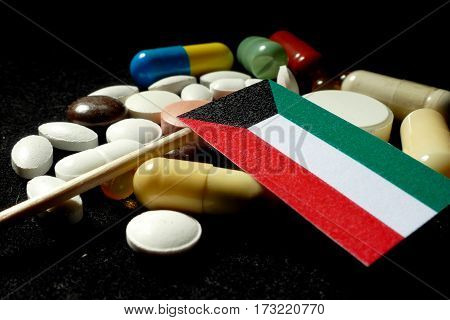 Kuwaiti Flag With Lot Of Medical Pills Isolated On Black Background
