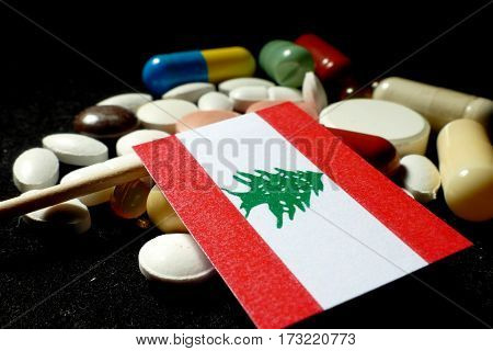 Lebanese Flag With Lot Of Medical Pills Isolated On Black Background