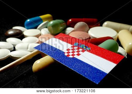 Croatian Flag With Lot Of Medical Pills Isolated On Black Background
