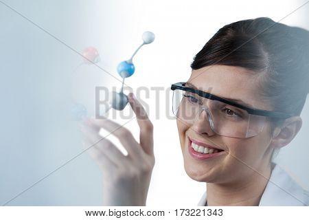 Female scientist holding molecular model against white background
