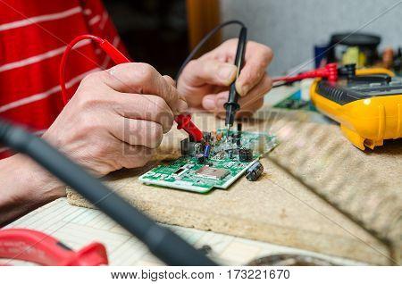 man hands closeup repair electronic device using Multimetr