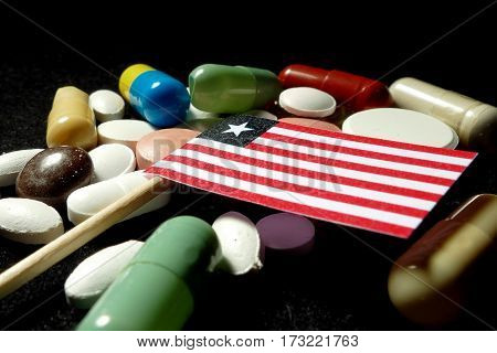 Liberian Flag With Lot Of Medical Pills Isolated On Black Background