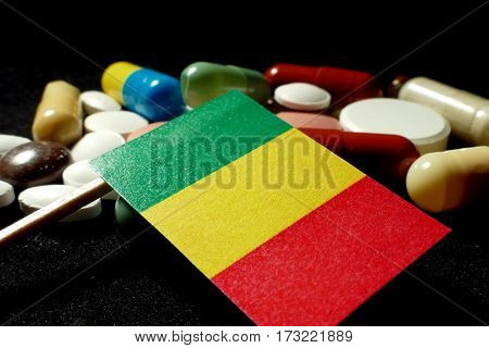 Malian Flag With Lot Of Medical Pills Isolated On Black Background