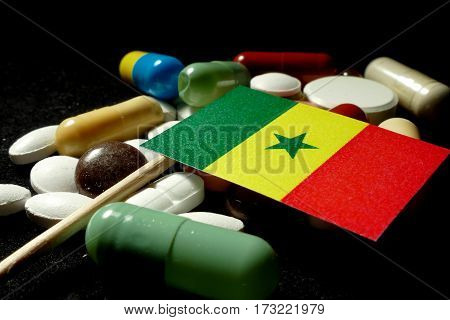 Senegalese Flag With Lot Of Medical Pills Isolated On Black Background
