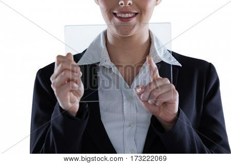 Businesswoman pretending to use digital tablet against white background