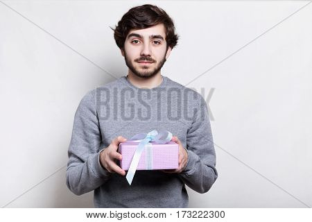 Studio portrait of handsome bearded man with trendy hairstyle dressed in casual clothes holding present in his hands looking directly into camera isolated over white background