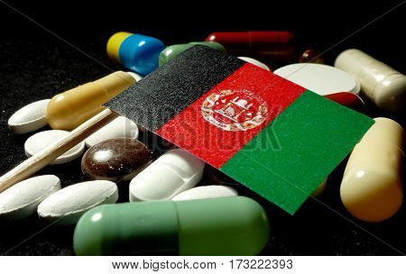 Afghan Flag With Lot Of Medical Pills Isolated On Black Background