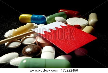 Bahraini Flag With Lot Of Medical Pills Isolated On Black Background