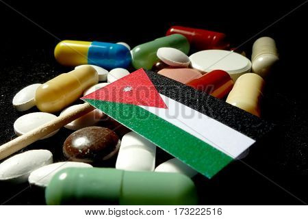 Jordanian Flag With Lot Of Medical Pills Isolated On Black Background
