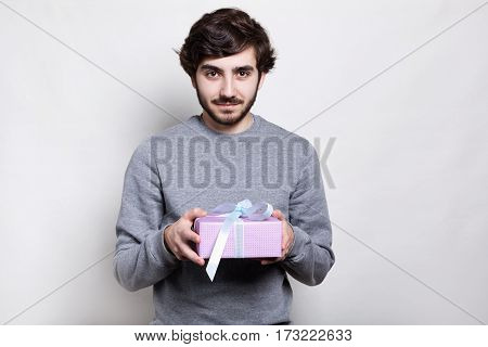 Hipster young bearded man dressed in grey sweater holding a wrapped gift isolated over white background. A gift box for lover. A guy with present having pleased expression. Celebration concept