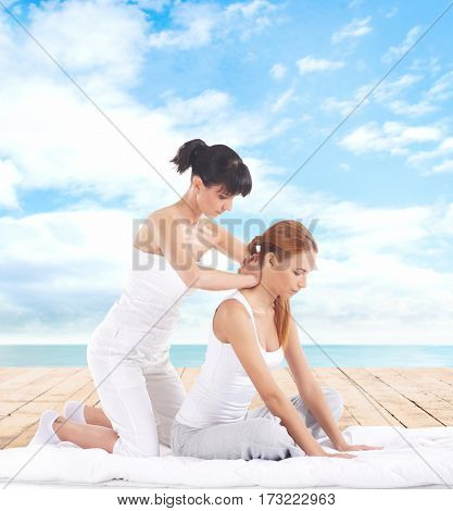 Young woman getting traditional Thai stretching massage by therapist on a pier
