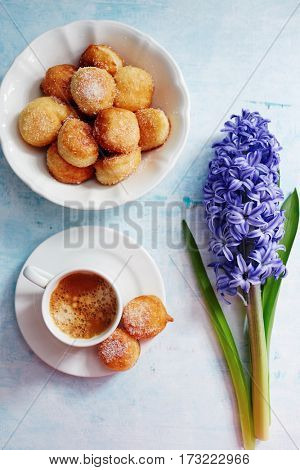 Freshly brewed espresso, small homemade doughnuts with icing sugar and flowers on blue table.
