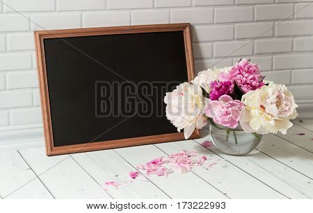 Beautiful bouquet of pink and white peonies in the glass vase with scattered petals and black chalkboard with empty place for your text on the white brick and wood background.