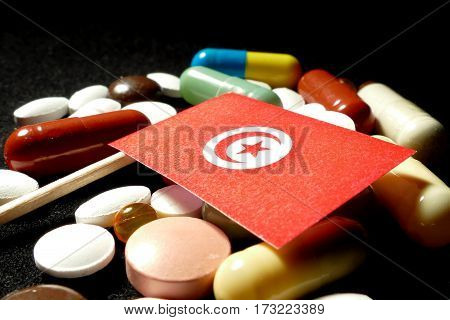 Tunisian Flag With Lot Of Medical Pills Isolated On Black Background