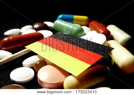 German Flag With Lot Of Medical Pills Isolated On Black Background