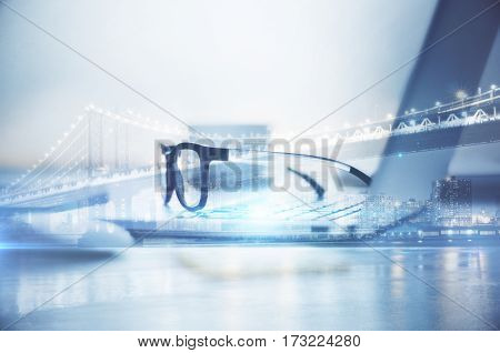 Side view of notebook with spectacles on abstract city background. Work concept. Double exposure
