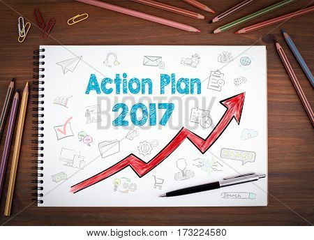 Action Plan 2017. Notebooks, pen and colored pencils on a wooden table.