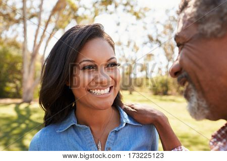 Father And Adult Daughter Talking In Park Together
