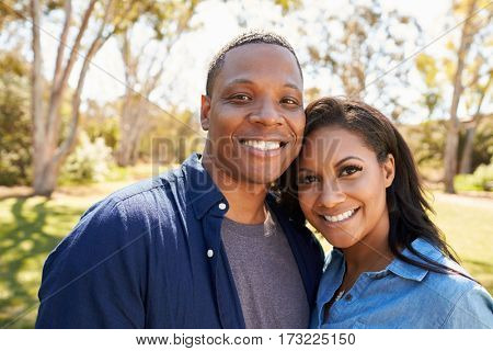 Outdoor Head And Shoulders Portrait Of Couple In Park