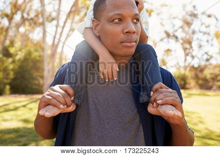 Close Up Of Father Carrying Son On Shoulders Walking In Park