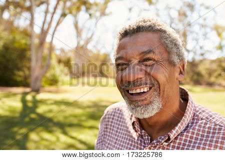 Outdoor Head And Shoulders Shot Of Mature Man In Park