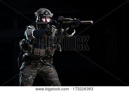 Man in body armor helmet with rifle on dark background