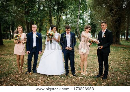 Wedding Couple With Bridesmaids And Best Mans Drink Champagne At Park.