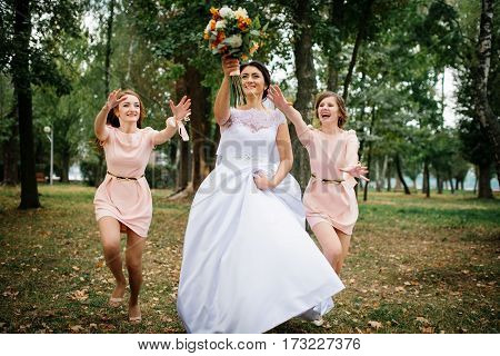 Bride With Bridesmaids Throw Bouquet At Wedding Day.