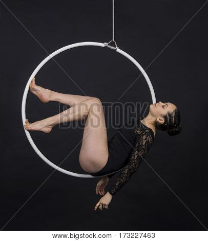 Aerial acrobat in the ring. A young girl performs the acrobatic elements in the air ring. Studio shooting performances on a black background.
