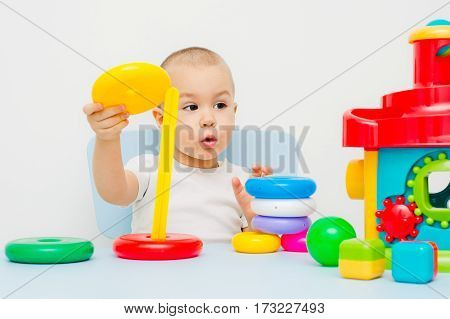 Child collects a pyramid on a table on a white background