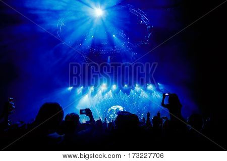 Girl, Close up of recording video with smartphone during a concert. Toned picture