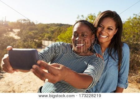 Mother And Adult Daughter Taking Selfie With Phone On Walk