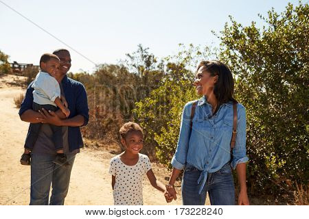 Family Walking Along Track In Countryside Together