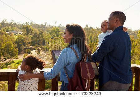 Family Standing On Outdoor Observation Deck Looking At View