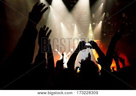 Take photo by smartphone in front of concert stage, during the light show