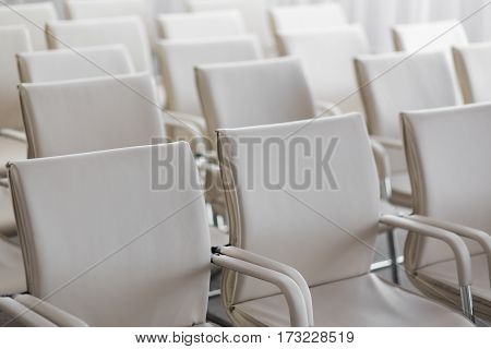 background of row of white seats. Empty hairs in the conference hall.