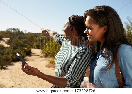 Mother And Adult Daughter Navigate With Mobile Phone On Walk
