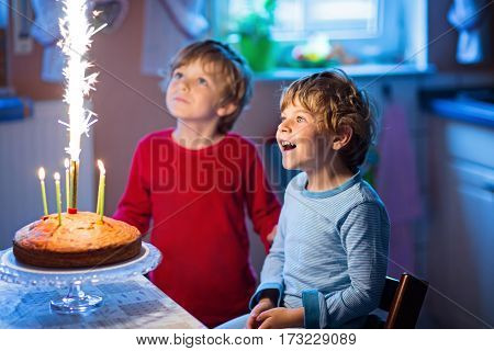 Beautiful kids, little boys celebrating birthday and blowing candles on homemade baked cake, indoor. Birthday party for siblings hildren. Happy twins about gifts and frirework
