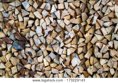 Wooden texture background broun firewood. Stacked firewood pattern