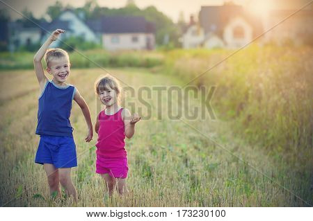 Two happy joyful merry children boy and girl brother and sister standing in wheat field with blurred houses on background and having fun