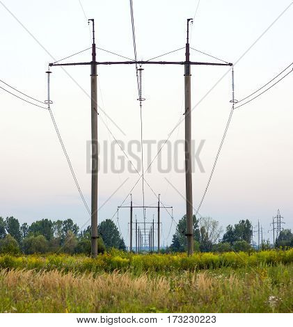 Electricity Pylons Trailing Away in Field. Power-transmission poles in the nature environment.