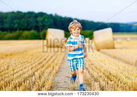 Adorable little kid boy running in wheat field with hay bales. Active outdoors leisure with children on warm summer day. child having fun