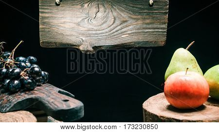 Traditional wood sign hanging above wood boards with apples, pears and grapes. Isolated over black background
