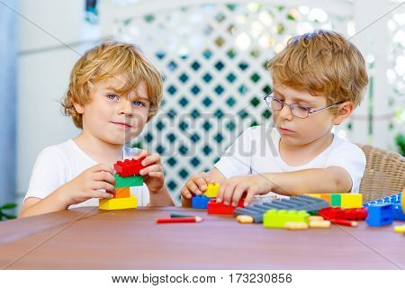 Two little blond preschool kids boys playing with lots of colorful plastic blocks. Active children, brothers, friends and siblings having fun with building and creating together. Education, skills.