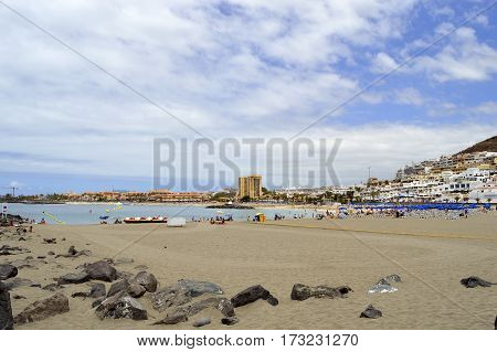 Los Cristianos beach Tenerife Canary Islands Spain Europe - June 13 2016: Tourists on the beach enjoying the sun