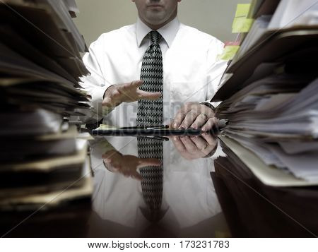 Businessman at desk with piles of files, papers and a notebook pen