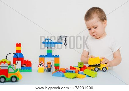 little boy playing in bright designer on a white background